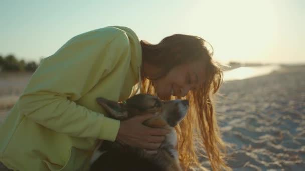 Kaukasische Hündin streichelt ihren Hund, während sie sich morgens am Sandstrand am Meer ausruht