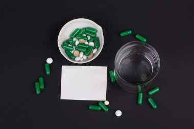 pills with glass of water to drink the pills on dark black background. Pain