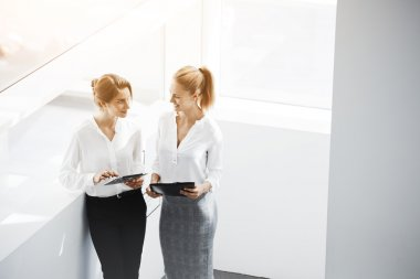 Businesswoman is holding folder, while her secretary is searching information