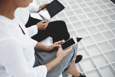 Women are working on smart phone and digital tablet