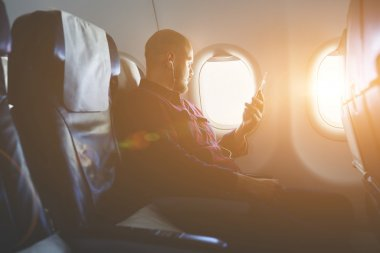 Young hipster guy in headphones in plane