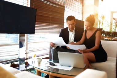 Young man and woman working together with paper documents before meeting with partners