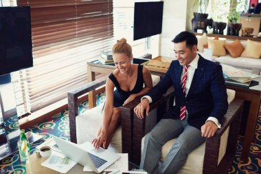 Cheerful woman and man skilled economists are using net-book during meeting in an informal setting