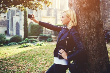 Attractive woman traveler is photographing herself on cell telephone during her walking