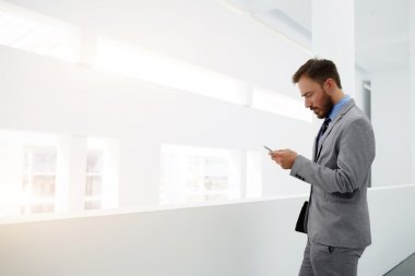 Young male is using cell telephone, while is standing in office interior near copy space for your advertising content