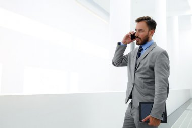 Young male skilled manager is calling via mobile phone during break at job
