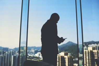 Male manager is standing in his office near big window with view of business district in China