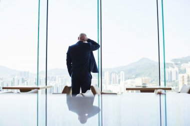 Businessman is standing near office window with view of Hong Kong city