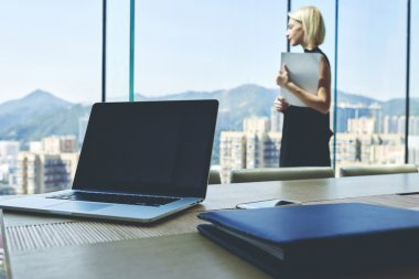 Young skilled businesswoman standing in her private office