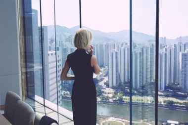 Female CEO is calling via cell telephone, while is standing in office interior near window with cityscape view and copy space