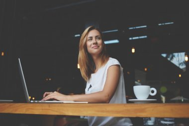 Beautiful woman successful freelancer using laptop computer while sitting in coffee shop