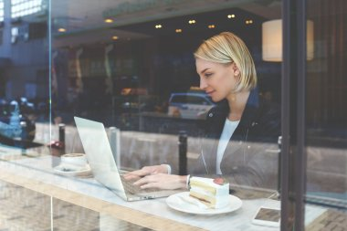 Young hipster girl is working on net-book, while is sitting in modern hipster coffee shop interior