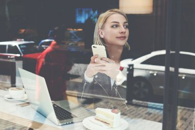 Young woman is using mobile phone, while is sitting in modern cafe-bar with portable laptop computer