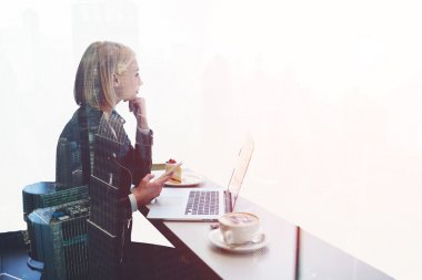 Woman freelancer using cell phone and net-book