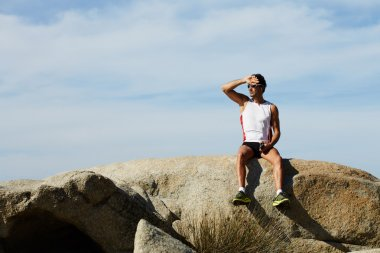 Attractive runner resting sitting on big rock at sunny day