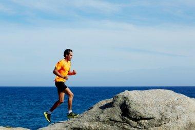 Runner in fluorescent t-shirt runs over sea rocks at morning jog