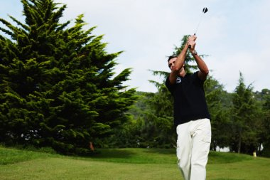 Attractive golfer hitting with club standing on the course