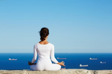 Young woman practices yoga on high altitude with sea ships view on background