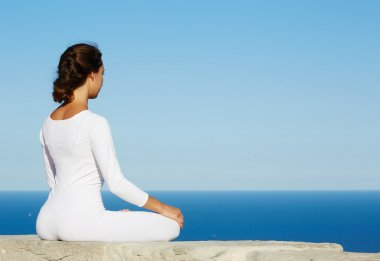 Young woman seeking enlightenment through meditation practice yoga outdoors