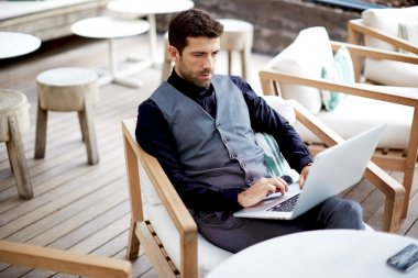 Handsome hipster man working with his laptop on the beautiful restaurant, work everywhere
