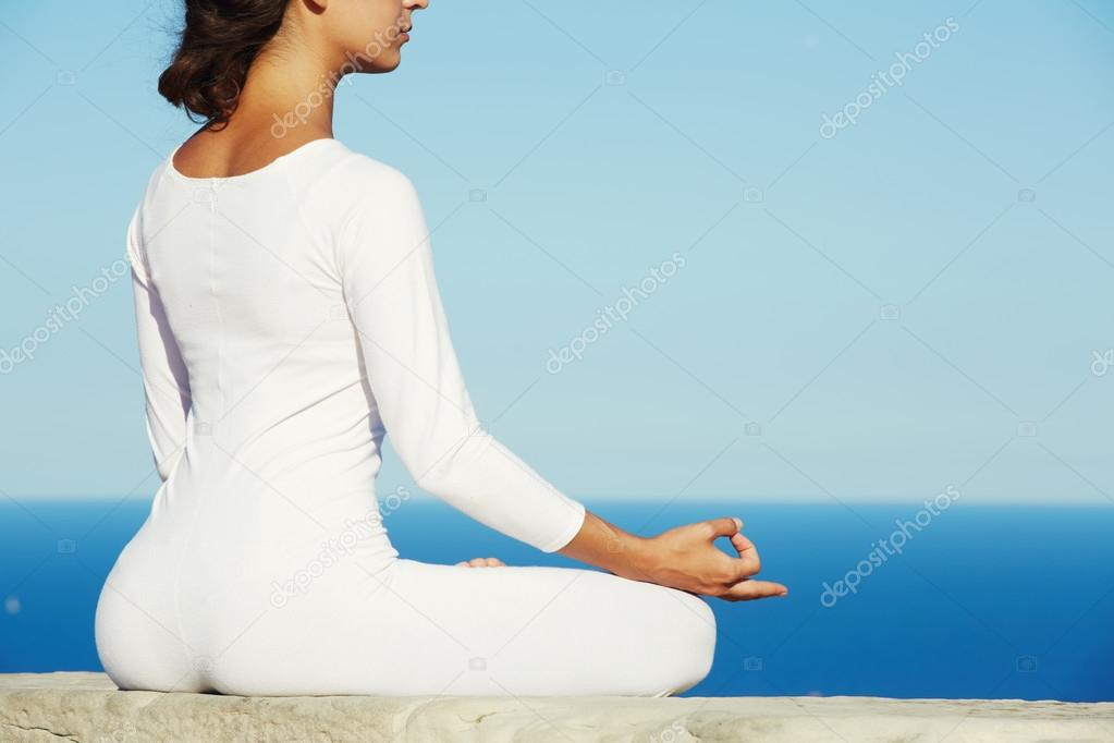 Brunette woman makes yoga meditation on high altitude with blue sea on background at sunny evening