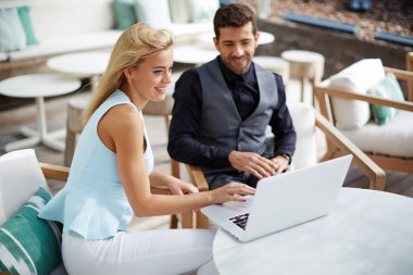 Business team of two successful people sitting outdoors in lounge terrace and planning work, businessman and businesswoman meeting in modern cafe, business partners having working with computer