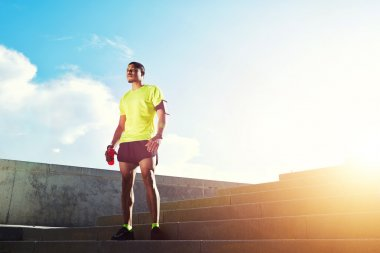 Young dark skinned jogger with muscular strong standing against soft sunset light outdoors, beautiful fit man in bright fluorescent sportswear, sports fitness concept