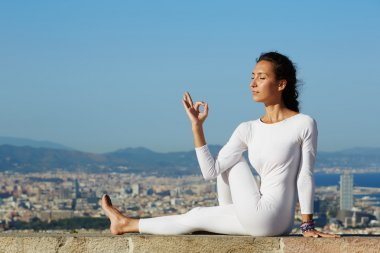 Yoga on high altitude with big city on background, young woman seated in yoga pose on amazing city background, woman meditating yoga and enjoying sunny evening, woman makes yoga on mountain hill