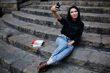 Young charming girl smiling while taking a self-ie outdoors,smiling student girl making a self portrait with smart phone sitting on steps, beautiful young hipster girl photographing herself with phone stock vector