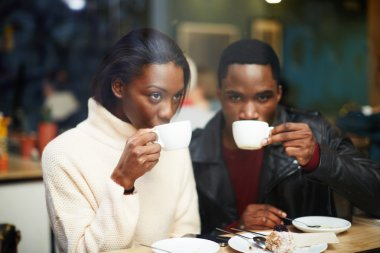 Friends enjoying coffee in beautiful place, cold winter days in beautiful coffee shop, friends at breakfast having coffee and enjoying themselves, two young friends holding cups drink coffee in cafe