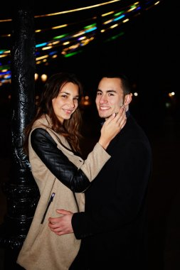 Young couple walking on a city embraces and enjoy each other