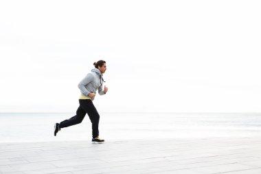 Young man running along the beach