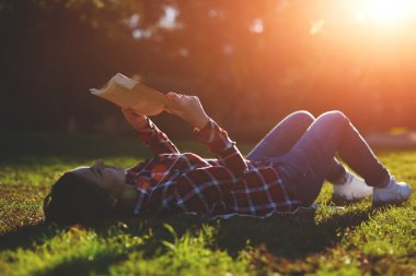 Woman lying on the grass and reading a book