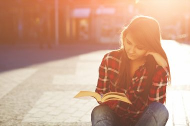 hipster woman enjoying a good book sitting at sunny evening outdoors