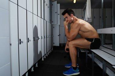 Athlete sitting in gym's locker room