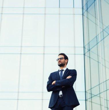 business man in glasses standing near skyscraper