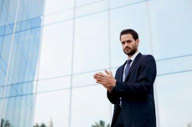 businessman in suit rubs his hands