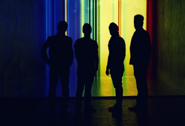 Silhouettes of four men standing on a bright moving background