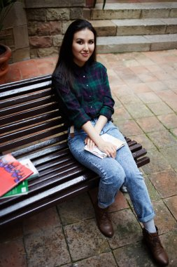 Аttractive college student relaxing on a bench outdoors