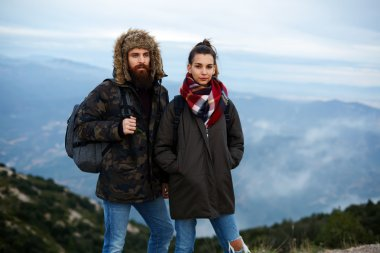 Backpackers standing on top of a mountain against foggy valley
