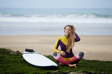 A girl in a bright dress for riding a surfboard sits on the beach after the conquered wave