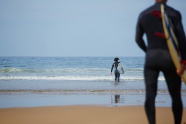 Male surfers carrying their surfboards