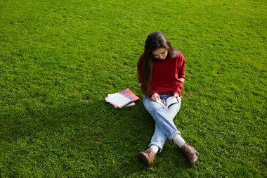 Girl sitting on the grass reading a book