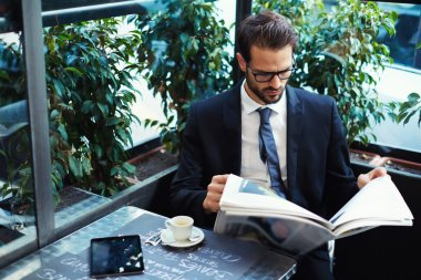 Handsome businessman reading a newspaper