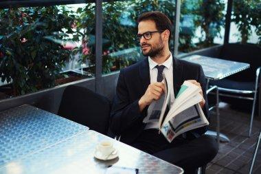 Businessman holding a newspaper outdoors