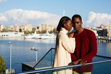 Couple hugging on modern balcony