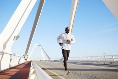 Athletic male running on a bridge