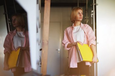 Woman holding bright yellow book