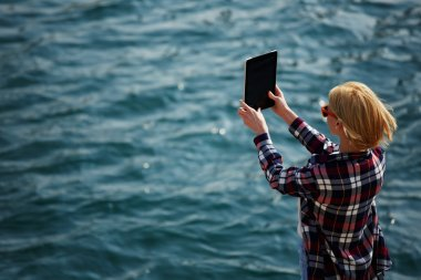 Woman taking picture with a digital tablet