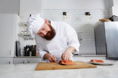 Chef cook in uniform diligently cutting salmon